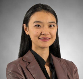 Dr. Carrot-Zhang smiling with brown jacket and grey background