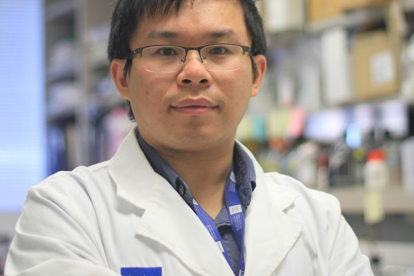 Dr. Xia posing with white jacket in lab