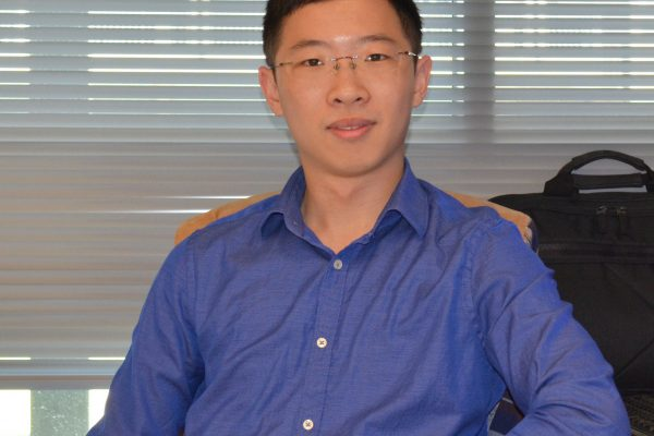 Dr. Wu smiling with blue shirt and office background