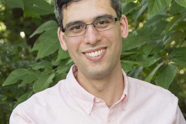 Dr. Schwartz smiling with foliage background and pink shirt